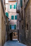 Medieval street and old houses in Siena, Italy Stock Photos