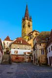 Medieval street in Sibiu, Transylvania, Romania. Medieval street with Evanghelical Church's famous tower, landmark of Sibiu Stock Image