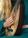 Medieval strings instrument played by a girl with delicate hands. Detail on a strings medieval musical instrument played by young girl in emerald dress royalty free stock photography