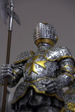 Medieval Suit of Armor. Medieval knight in suit of armor with gold maltese cross design on the front. Knight is holding a battle axe royalty free stock photography