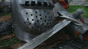 Medieval Sword close up - camera slide. Medieval plate armor with a sword, chain mail and helmet lying on the grass stock video footage
