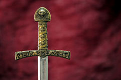 Medieval sword. Replica over dark red background royalty free stock photo
