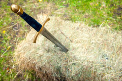 Medieval sword stuck in a pile of hay Royalty Free Stock Photography