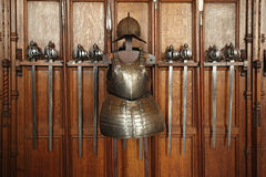 Medieval swords and armor. Medieval swords, spears, and body armor in a wooden display rack Royalty Free Stock Images