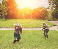 Medieval tournament between two knights. Two medieval knights in armor with swords and helmets are fighting on green grass Royalty Free Stock Photo
