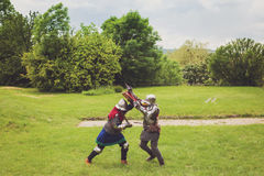 Medieval tournament between two knights. Two medieval knights in armor with swords and helmets are fighting on green grass Royalty Free Stock Image