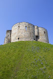 Medieval tower. Bluebells and wildflowers growing on the grassy banks of the medieval landmark of cliffords tower in the heart of the ancient city of york Royalty Free Stock Photography