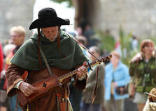 Medieval troubadour. Tunning his traditional string instrument during  Week-end de L'ascension-Grand Fete medievale in Nogent de Rotrou, France, 13-16.05.2010 Royalty Free Stock Images