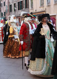 Medieval Venetian parade. Venice, Italy- February 26th, 2011: Image of a group of disguised people walking together during the Carnival of Venice.The Carnival of Royalty Free Stock Images