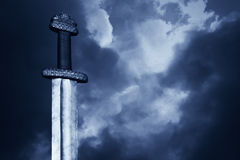 Medieval viking sword against a dramatic sky. War symbol. Medieval viking sword against a dramatic sky stock photos