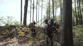 Vikings running in the forest to fight in a battle. Medieval Vikings running in the forest to fight in a battle. Vikings clad in chain mail, with shields, swords stock video