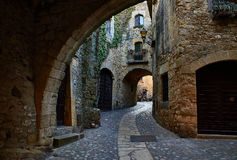 The medieval village of Pals. Girona, Spain. Pals, Spain - June 22, 2017. Doorgang of Carrer Major street in the medieval historic downtown of Pals. Bajo Stock Photos
