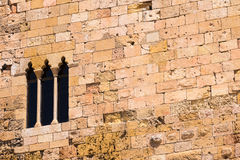 The medieval wall of the building. Stone wall with windows, Tarragona, Catalunya, Spain. Wall of the Old City. Copy space. Stock Photo