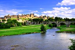 Medieval walled city of Carcassonne, France with historic bridge. View of the medieval walled city of Carcassonne, France from a riverside park with historic Royalty Free Stock Photos