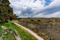 Medieval walls of Rhodes and moat under cloudy sky, Greece Stock Photo