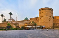 The medieval walls of Saladin Citadel hide its main landmarks - the Alabaster Mosque with tall minarets and Al-Nasir Muhammad. Mosque with mosaic green dome stock photo