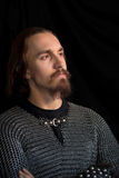Medieval warrior. With beard in chain armour over black background looking ahead Stock Photography