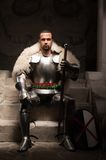 Medieval warrior in armor and fur mantle. Full length portrait of medieval warrior in armor and fur mantle sitting on steps of temple with sword and shield Stock Images