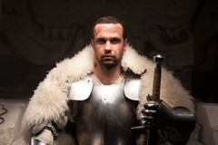 Medieval warrior in armor and fur mantle. Waistup portrait of medieval warrior in armor and fur mantle with sword looking vigorously at camera, dark background Royalty Free Stock Photography