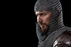 Medieval Warrior with chain mail armour and red Cloak. Portrait of Medieval Warrior with chain mail armour and red Cloak. Black Background stock image