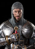 Medieval Warrior with chain mail armour and Sword. Portrait of Medieval Dirty Face Warrior with chain mail armour and Sword in hands. Black Background Stock Photos