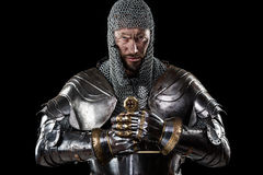 Medieval Warrior with Chain Mail Armour and Sword. Portrait of Medieval Dirty Face Warrior with chain mail armour and red cross on sword. Black Background Stock Photography