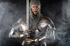 Medieval Warrior with Chain Mail Armour and Sword. Portrait of Medieval Dirty Face Warrior with chain mail armour and red cross on sword. Cloud smoke on Dark Royalty Free Stock Photo