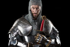Medieval Warrior with chain mail armour and sword. Portrait of Medieval Dirty Face Warrior with chain mail armour and red cross on sword. Dark Background royalty free stock image