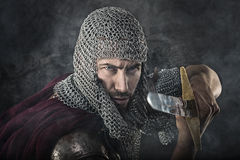 Medieval Warrior with chain mail armour and sword. Portrait of Medieval Dirty Face Warrior with chain mail armour and sword. Smoke Cloud on Dark Background Stock Photos