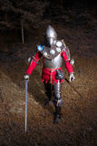 Medieval Warrior in Knight's Suit Standing in Dark Forest Ready for Battle, Full Length Shot Royalty Free Stock Image
