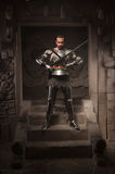Medieval warrior posing on steps of ancient temple Royalty Free Stock Image