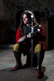 Medieval Warrior With Sword Sitting in Old Church Looking Away royalty free stock images
