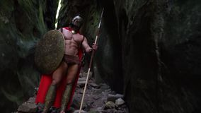 Medieval warrior in the woods. Medieval spartan warrior in a helmet hiding behind his shield ready to attack the enemy with his spear strength bravery heroic stock video