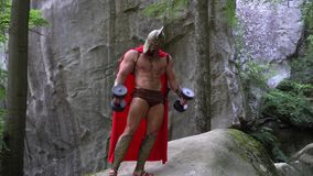 Medieval warrior in working out in the woods. Full length shot of a powerful muscular spartan warrior in a helmet and red cape exercising outdoors in the forest stock video