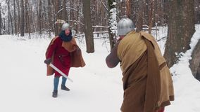 Medieval irish and frankish warriors in armor fighting in a winter forest with swords and shields stock video