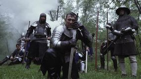 Medieval warriors in metal chainplate armor in the forest under rain