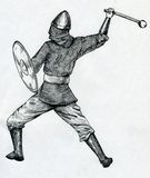 Medieval warriow with a club. Medieval warrior - man or woman - wearing chainmail vest, leather boots, bracers and helmet and wielding shield and club. Hand Stock Photo