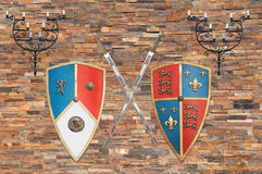 Medieval weapons and candleholders on a brick wall. Shields, swords and candleholders of the average age of the kingdom of Castile and Leon, Spain, are hanging stock photos