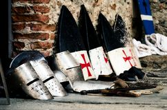 Medieval armory in a castle. Medieval weapons, shields and helmets from the crusade age on a castle floor during an historical reenactment Royalty Free Stock Photos