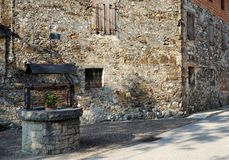 Medieval well with an old stone building on background stock photography