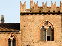 Medieval window with high battlements. Photo made in Mantua in Lombardy (Italy). Since July 2008 the city of art with Sabbioneta Lombard, both united by the Stock Photo
