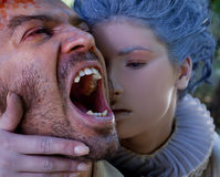 Medieval woman embracing male vampire. Close-up of medieval women embracing wounded male vampire Stock Photo