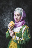Medieval woman holding a burger.anachronism. Medieval woman holding a burger.. In the old beautiful yellow-green dress. Historic image. Gothic. Europe Royalty Free Stock Images