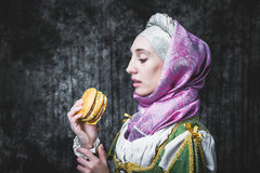 Medieval woman holding a burger.anachronism. Medieval woman holding a burger.. In the old beautiful yellow-green dress. Historic image. Gothic. Europe Stock Image