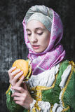 Medieval woman holding a burger.anachronism. Medieval woman holding a burger.. In the old beautiful yellow-green dress. Historic image. Gothic. Europe Stock Photography