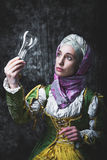 Medieval woman holding an electric lamp Stock Photos