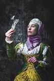 Medieval woman holding an electric lamp Royalty Free Stock Photos