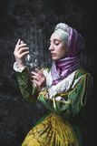 Medieval woman holding an electric lamp Stock Photography