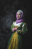 Medieval woman holding hands in prayer. Pray. In the old beautiful yellow-green dress. Historic image. Gothic. Europe Royalty Free Stock Image