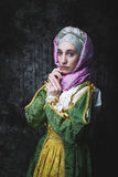 Medieval woman holding hands in prayer. Pray. In the old beautiful yellow-green dress. Historic image. Gothic. Europe Royalty Free Stock Photo
